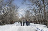 Stock Photo of winter scenery with snow on the ground. a family, adults and two children, wa