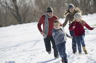 Stock Photo of winter scenery with snow on the ground. family walk. two adults chasing two c