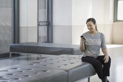 Urban lifestyle. a young woman sitting on a seat in a building, using her mob Stock Photos