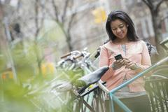 city life in spring. a young woman in a peach coloured shirt, using her smart - stock photo