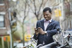 City life in spring. a young man in a blue suit, by a bicycle park. checking  Stock Photos