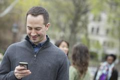 A group of people in a city park. a man in a grey sweater, checking his phone Stock Photos