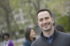 A group of people in a city park. a man in a grey sweater, smiling. Stock Photos