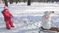Child Pulls Snowman in Sledge, Sleigh, Sled, Little Girl Playing in Snow, Winter Stock Footage