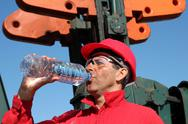 Stock Photo of Thirsty Oil Industry Worker