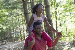 A man giving a young girl a piggyback. Stock Photos