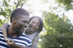 Stock Photo of a man giving a child a piggyback, in the shade of trees on a summer day.