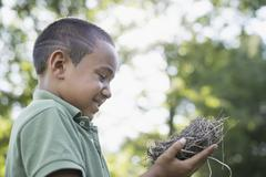a young boy outdoors on a summer day, holding a bird nest. - stock photo