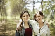 Stock Photo of two girls, friends smiling with their arms around each other.