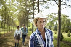 A group of friends walking down an avenue of trees in woodland. Stock Photos