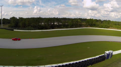 Ferrari speeds through turns on race track, aerial view Stock Footage