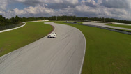 Flyin low over a Ferrari on a race track, aerial view Stock Footage