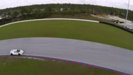 A White Ferrari on race track, aerial view of car going through a turn Stock Footage