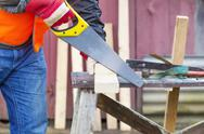 Stock Photo of Carpenter sawing plank on to the work table