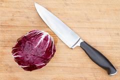 red radicchio with a kitchen knife - stock photo