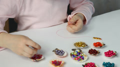 Unrecognizable little girl threading beads and making bracelet Stock Footage