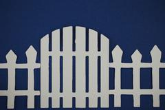 Paper cut out of gate of white picket fence - stock photo
