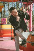 portrait of a handsome young man on amusement ride - stock photo