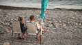 Couple enjoying summer beach vacation seated on deckchairs Footage