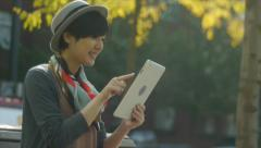 Woman Sitting On A bench Using A Digital Tablet (bike passes by) Stock Footage