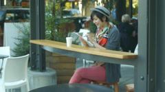 Stock Video Footage of Woman Using Her Digital Tablet At Urban Cafe (with background activity)