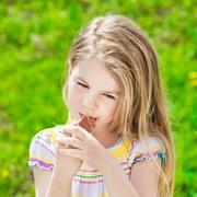 pretty blond little girl with long hair eating ice-cream in summer sunny day - stock photo