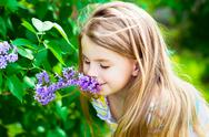 Stock Photo of beautiful blond little girl with long hair smelling flower