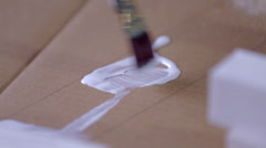 Brushing Glue on Paperboard - stock footage