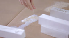 Creating Sand Decoration on Paperboard Building Model - stock footage