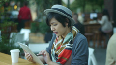 Japanese Woman At An Open Air Cafe Counter With Her Digital Tablet (Side View) Stock Footage