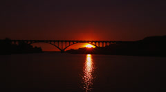 Dramatic Sunset Behind Arched Bridge - stock footage