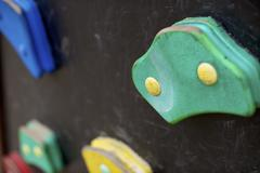 Artificial climbing wall covered with colored holds in an adventure playground. Stock Photos