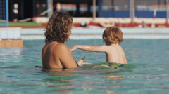 Slow-Mo: Happy Mother Playing With Child In The Pool Stock Footage