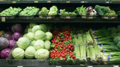 Medium tracking shot of vegetables in a grocery store - stock footage