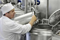 Worker on a milk factory Stock Photos