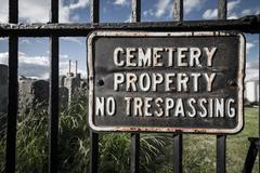 no trespassing sign on cemetary fence - stock photo