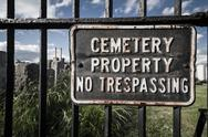 Stock Photo of no trespassing sign on cemetary fence