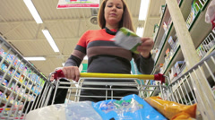 Young woman adding goods with shopping cart in wholesale market - stock footage