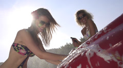 SLOW MOTION: Sexy young women washing a car Stock Footage