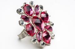 macro shot of fake rubby ring on white. - stock photo