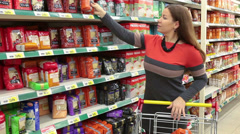 Young woman with shopping cart taking goods in wholesale market - stock footage