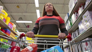 Stock Video Footage of Attractive woman with shop trolley purchasing in wholesale market