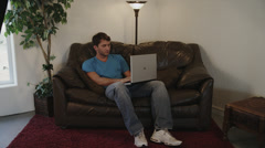 College Guy on Laptop Sitting on Sofa Stock Footage