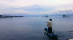 Fisherman in a small boat with his traps at lake Stock Footage