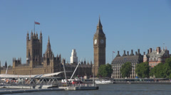 Palace Westminster Tower Clock Big Ben facade blue sky boat Thames River London  Stock Footage
