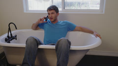 Man on Cell Phone Sitting in Empty Tub Stock Footage