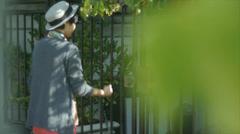 Woman On Her Phone, Walking Away Down A Tree-Lined Urban Sidewalk - stock footage