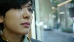 Stock Video Footage of Close Up Of A Young Woman Riding A Train, Looking Out At Cars & Storefronts