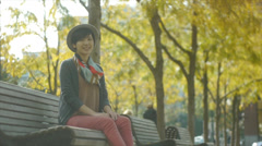 Portrait of A Smiling Young Asian Woman On A Park Bench (Background People) Stock Footage