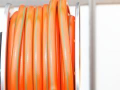 rolled up of orange plastic hose - stock photo